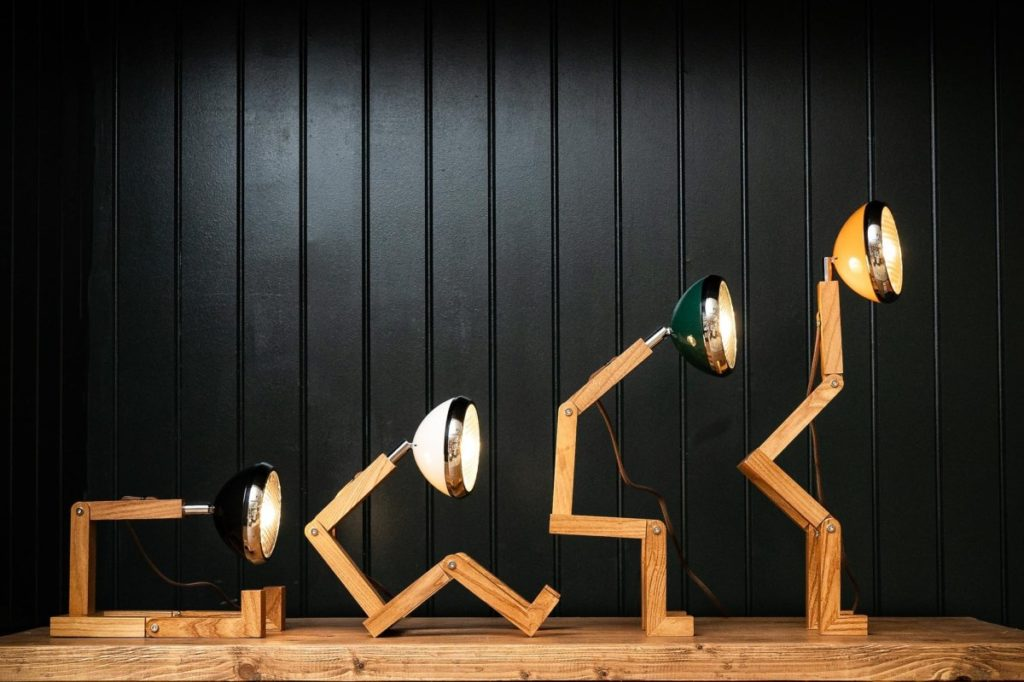 Lampada di legno e alluminio a forma di omino snodabile. La lampada si ispira ai fari delle vecchie amate vespe Piaggio.
